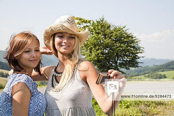 zwei Frauen  die die Selbstporträt mit Digitalkamera