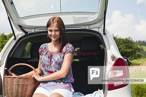Porträt der Frau mit Picknick-Baset auf Auto