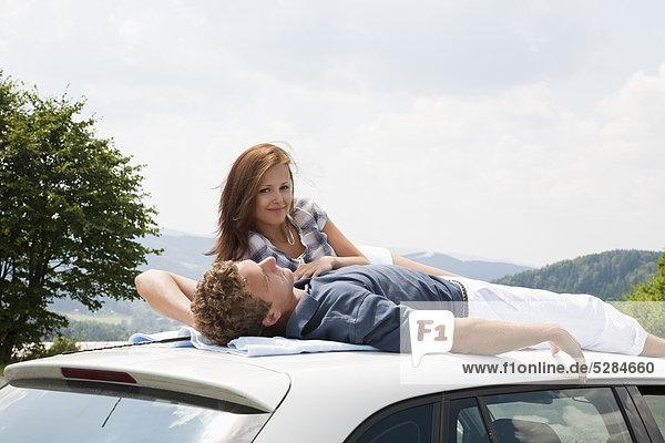junges Paar am Dach des Autos