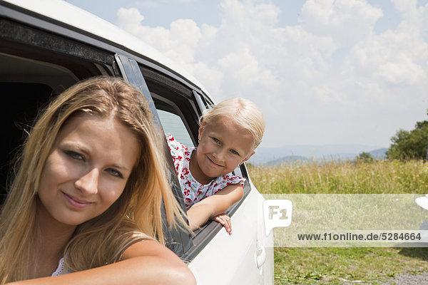 Porträt der jungen Frau und Tochter Blick aus dem Autofenster