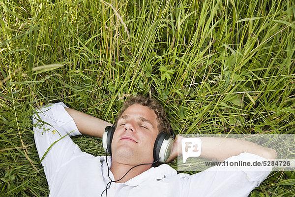 Portrait of young Man lying in Grass anhören von Musik