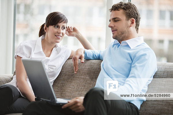 young couple at home sitting in front of laptop computer
