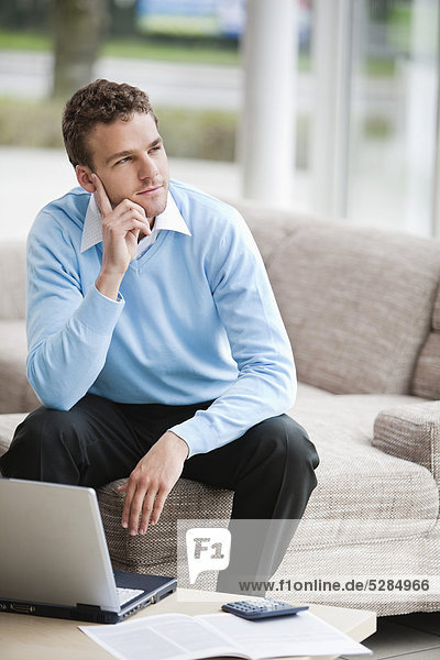 portrait of young man with laptop computer at home