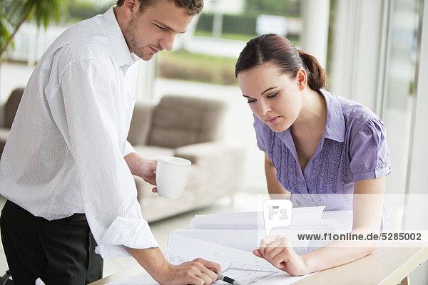 zwei Geschäftsleute an Tisch Blick auf Entwurf