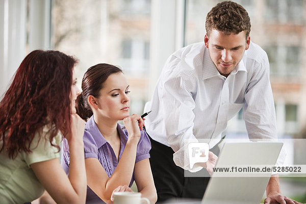 young businessman giving presentation to female colleagues