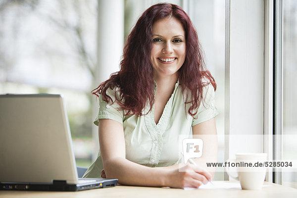 Porträt von roten Haaren geschäftsfrau arbeiten mit Laptop-computer