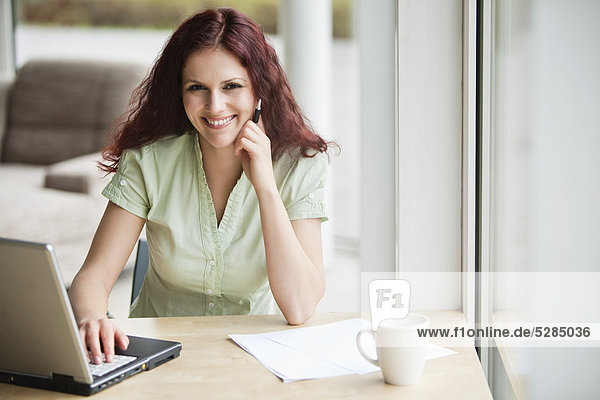 portrait of red haired businesswoman working with laptop computer