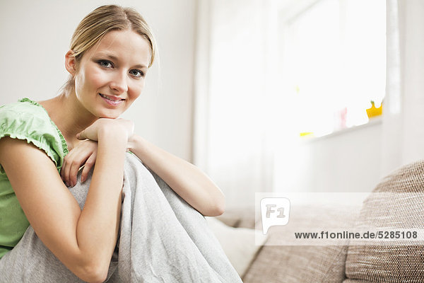portrait of young woman at home sitting on sofa