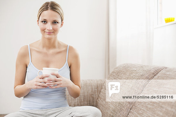 Portrait of young Woman with Kaffeetasse entspannend auf sofa