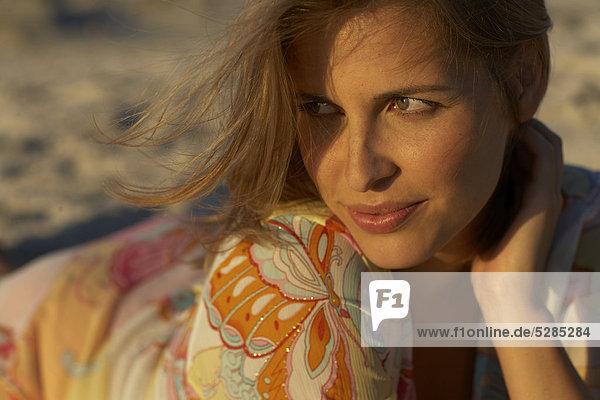 Beautiful Woman lying in Sand im Sonnenlicht verblassen