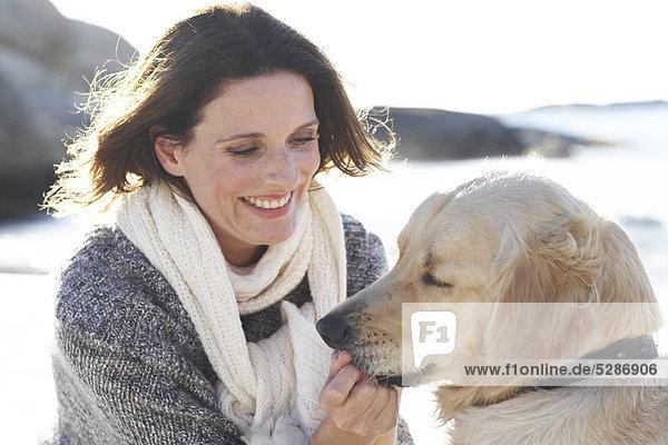 Landschaft der schöne Dame mit Hund am Strand spielen
