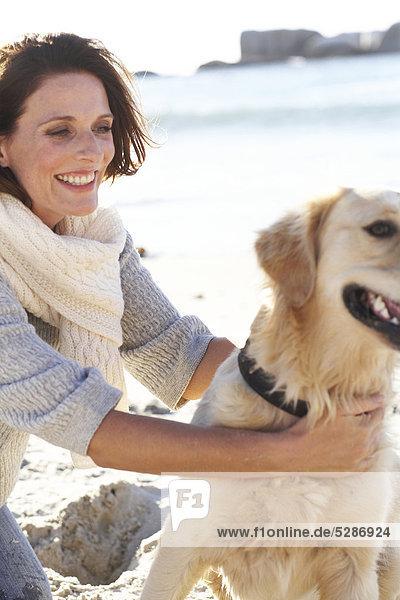 Schöne Dame mit Hund am Strand spielen