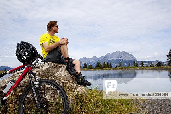 Mann mit Mountainbike an einem Felsen schaut sich um