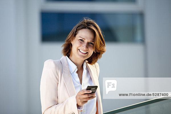 Lächelnde Geschäftsfrau mit Handy  Portrait