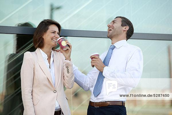 Geschäftsmann und Geschäftsfrau mit Coffee to Go unterhalten sich