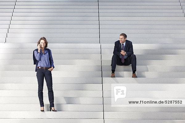 Geschäftsmann schaut auf telefonierende Geschäftsfrau auf einer Treppe