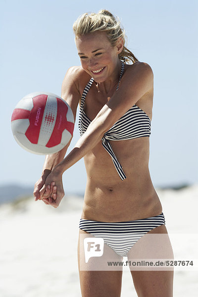 Portrait of beautiful girl playing vollyball on the beach