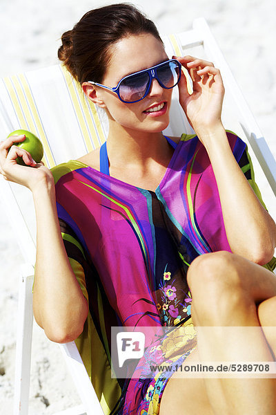 Beautiful woman in sitting in deck chair on sand while eating apple