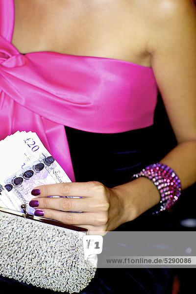 Glamorous Woman holding sparkly Silber Handtasche und Bargeld