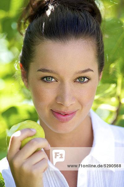 Porträt von eine schöne Brünette eating an apple