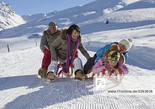 Großeltern mit Enkelkindern beim Schlittenfahren