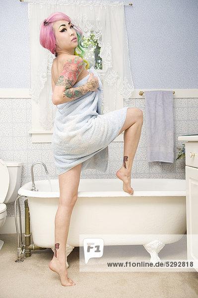 Junge Frau Handtuch posieren vor der Badewanne