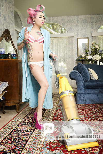 Woman In Bathrobe Smoking Cigarette While Cleaning Living Room With