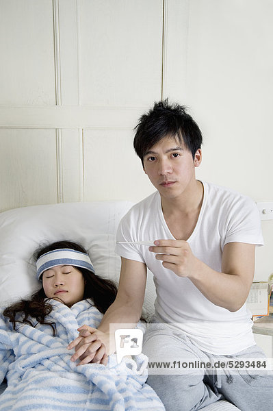 Portrait of young Man bei der Frau im Bett liegend