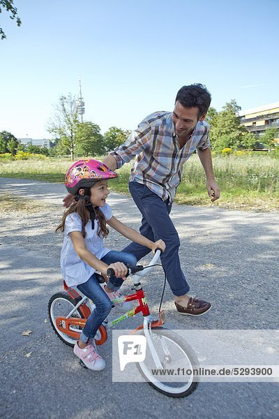 Vater rennt neben Tochter auf Fahrrad