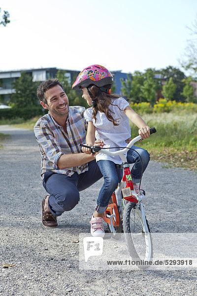 Vater hält Tochter auf Fahrrad im Freien
