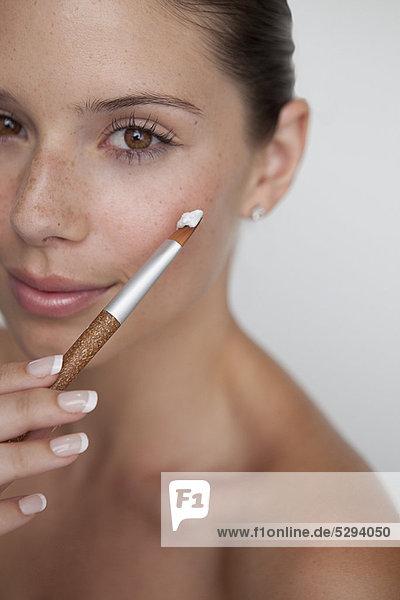 Frau hält Pinsel mit Make-up
