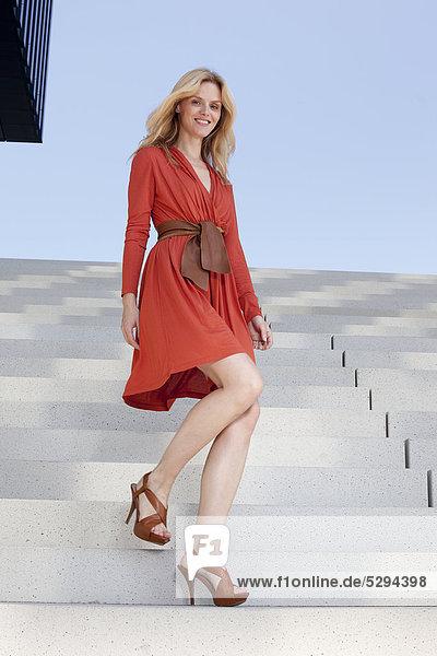 Frau in rotem Kleid geht auf einer Treppe