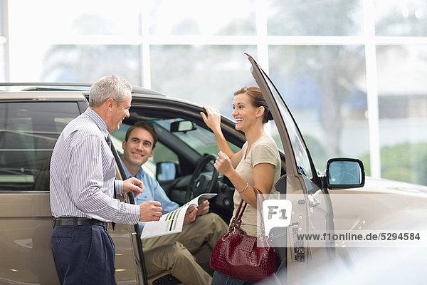Verkäufer zeigt Auto im Showroom