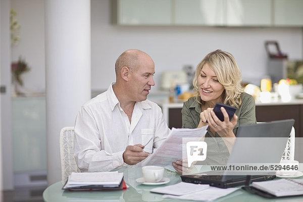 Ein Paar bezahlt seine Rechnungen zu Hause.