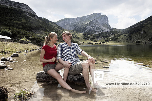 Couple relaxing in rocky lake