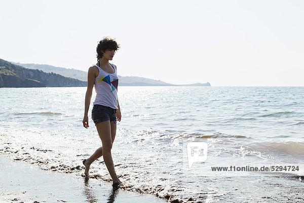 Frau geht in Wellen am Strand spazieren
