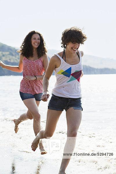 Frauen laufen in Wellen am Strand