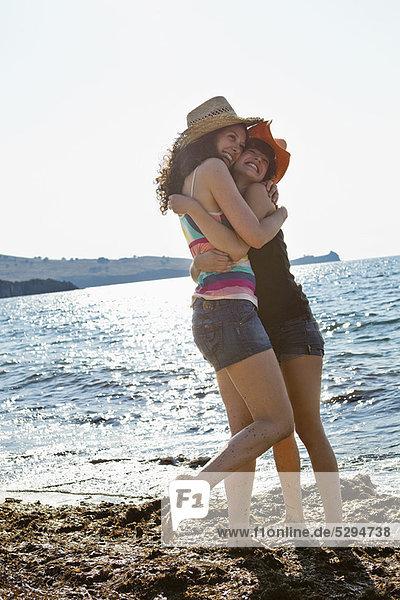 Women in sunhats hugging on beach