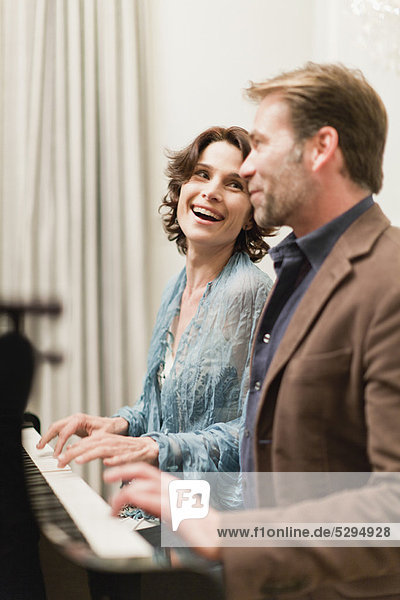 Couple playing piano together at home