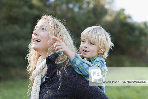 Mother carrying son piggyback outdoors