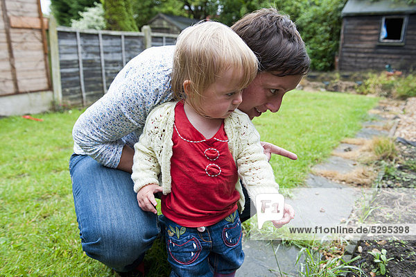 Mother and daughter exploring backyard