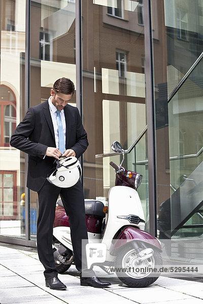 Geschäftsmann bindet Helm an Roller