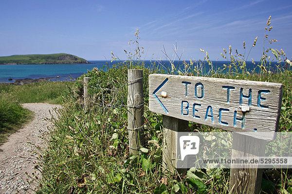 Schild mit Wegbeschreibung'zum Strand'.