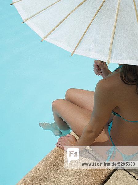 Frau sitzend am Pool unter dem Regenschirm