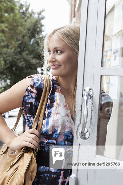 Woman carrying large purse in doorway