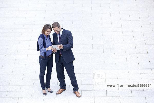 Geschäftsmann und Geschäftsfrau stehen mit Tablet PC im Freien