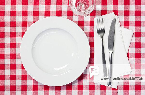 Gedeckter Tisch  Teller  Glas  Messer  Gabel  rotwei_ karierte Tischdecke