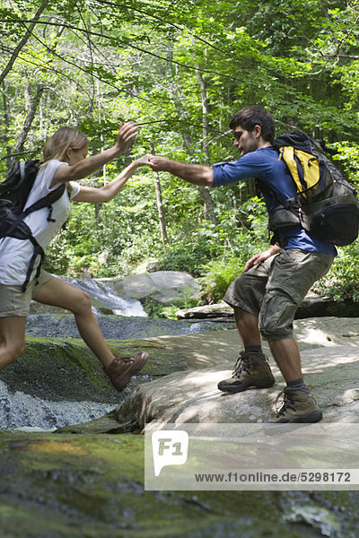 Mann hilft Frau beim Überqueren des Flusses