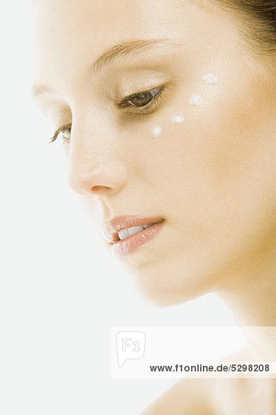 Frau mit Unteraugencreme unter dem Auge  Nahaufnahme