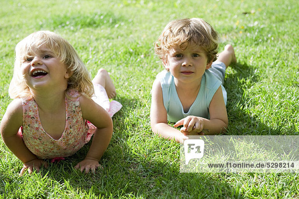 Young brother and sister lying on grass